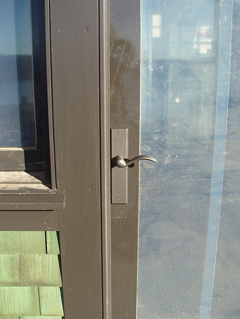 "Most of the window are covered with a protective plastic, and there is dust everywhere.  It will be fun to compare these photos with ""move-in day"" photos.   This door leads from the living room to our deck.  We have chosen ""Rocky Mountain"" door hardware."