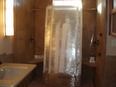 """This is the guest room bath... those are shower doors waiting to be installed.  We have chosen to use """"reed glass"""" so the hard water spots don't show sooo quickly..."""