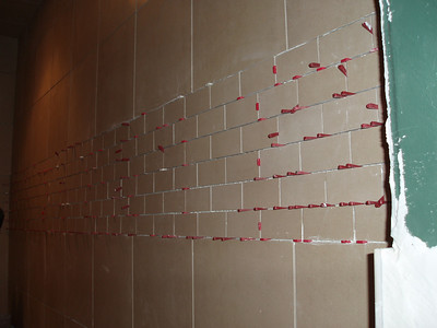 Did you ever wonder how they keep the tiles in place as they dry....all those little red wedges!  This is the wall detail in the steam shower.