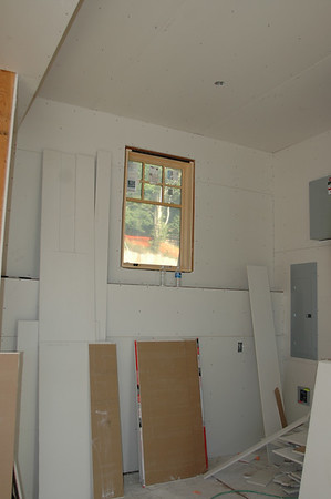 The first room to have dry wall hung is the utility room.  You can see the electrical boxes on the right.  To the left, out of site is the area where all the hot water and in-floor heating stuff will go.  The plumbers will come in soon and add the boiler to make sure everything is working perfectly, and to dry out the house completely before the dry-wall is sealed.