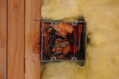 Did you ever wonder what was behind your light switches???  I think the orange foam is a recent addition.  Any place there was a big or small, and I mean small hole, this fire-retardant foam is applied.  The yellow fluffy stuff is insulation.