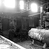 A photograph of the inside of the boiler room in the River Arts District in Asheville NC - a huge boiler. This building was once a part of a larger cotton mill district. The buildings have been abandoned since the 1950s. Almost the entire complex was burned to the ground in the 1990s. This building contains ice-making equipment that is at least 60 years old. The buildings, in most cases have been converted into artist studios. This one is still derelict.
