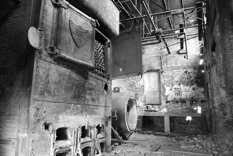 A photograph of the inside of the boiler room in the River Arts District in Asheville NC - a huge 10-15' boiler. This building was once a part of a larger cotton mill district. The buildings have been abandoned since the 1950s. Almost the entire complex was burned to the ground in the 1990s. This building contains ice-making equipment that is at least 60 years old. The buildings, in most cases have been converted into artist studios. This one is still derelict.