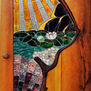 This door serves as entrance to a home yoga studio.<br /> <br /> The wood door that served as the basis for this work  was cut to allow a cedar branch to be embedded.. The space within the branch was then filled with the stained glass sun, pond, moon design.  <br /> <br /> A closeup photo of the door in this gallery shows details of this work.