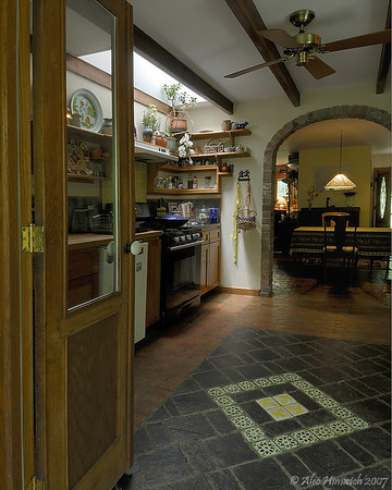 The tile floor, brick arch and shelving are all additions to this residential kitchen area.
