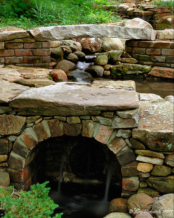 This is an excellent example of reuse of building materials.  This waterfall was built at a residence near Durham, NC.  The bricks in the intermediate pond and the arched waterfall of water exiting the pond were obtained from an abandoned house in Caswell County, NC while the stone bridge in the background was formerly a part of a curbside from a street in Durham, NC.