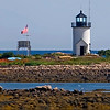 Goat Island Light. Located in Kennebunkport was built in 1835 and rebuilt in 1859. This brick lighthouse rests on an exposed natural ledge foundation. Accessible by boat only. This image was taken from the Cape Porpoise Pier with a long lens.