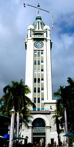 Aloha Tower  Aloha Tower, opened in 1926, symbolizes Honolulu's architectural skyline, and is widely recognized symbol of the hospitable Hawaiian Islands. The 10-story structure dominated the harbor landscape as the tallest building in the Territory of Hawaii for decades.   The clocks occupy the missing floors between the 9th floor office and the 10th floor observation deck of the Aloha Tower.  The Gothic tower has a mix of Art Deco elements. The tower offers spectacular views of the harbor and downtown Honolulu.   Although built primarily as a symbol, Aloha Tower also had a more practical function.  Rising opposite the entrance to Honolulu Harbor, it has a commanding view of the whole harbor and offers a front row seat for the excitement.  The tower also used to serve as a lighthouse and could be seen as far as 16 miles if out at sea.