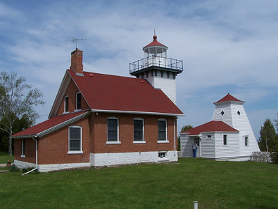 Sherwood Point Lighthouse at Sturgeon Bay, Wisconsin. A summer kitchen with sloping roof was added to the back of the original house.