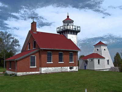 Sherwood Point Lighthouse: The white pyramid-shaped wooden fog signal building stands in front of the lighthouse. The original bell, which rang several times a minute to warn mariners in the area during fog conditions, was eventually replaced by compressed air foghorns, whose moan could be heard for ten miles.