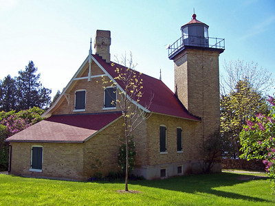 Eagle Bluff Lighthouse in  Peninsula State Park, Door County, Wisconsin. Built of Cream City brick brought by boat from Detroit, Michigan and MIlwaukee. The light tower is 43 feet tall, so the light shines 76 feet above the bay. It is topped by a ten-sided cast iron lantern room  The original Third-and-a-half order Fresnel Lens was replaced with a smaller Fifth Order Fresnel Lens in 1918. This lens remains in the lantern tower although it is no longer operational. The beam that shines across the bay each night is now powered by energy created from a small solar panel at the top of the tower.