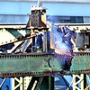 "Walsh Construction is overseeing the demolition of the old University Ave., Bridge. Demo work is being done by Jr Vinagro Recycling & Demolition. Here, ""Burner"" Jorge Martinez of Boston, cuts into a steel beam.  SUN/ David H. Brow"