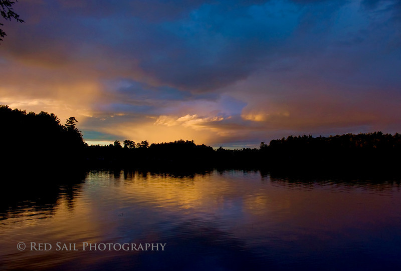 The setting sun lit up the sky and reflects on Parks Pond as a thunderstorm moves away.