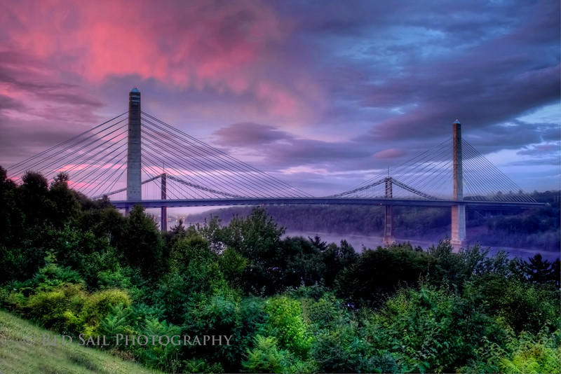 The Bucksport Bridge over the Penobscot River. HDR image (Photomatix) in tonemapped mode with Topaz smoothing filter applied.<br /> After a rainy day the setting sun lit up the sky.