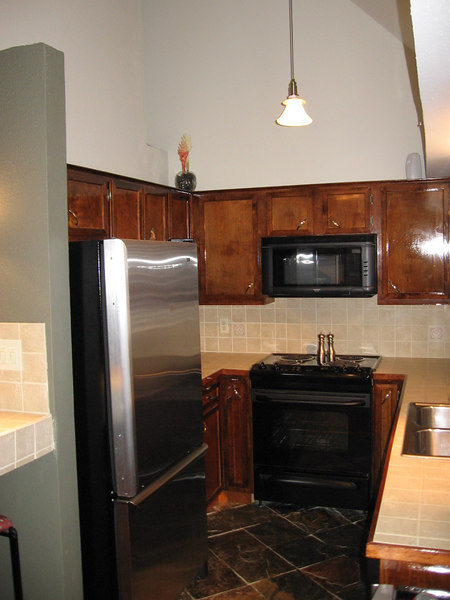 The kitchen includes the range and microwave. The cabinets have been refinished, the counters tiled, and the floors are slate tiles.