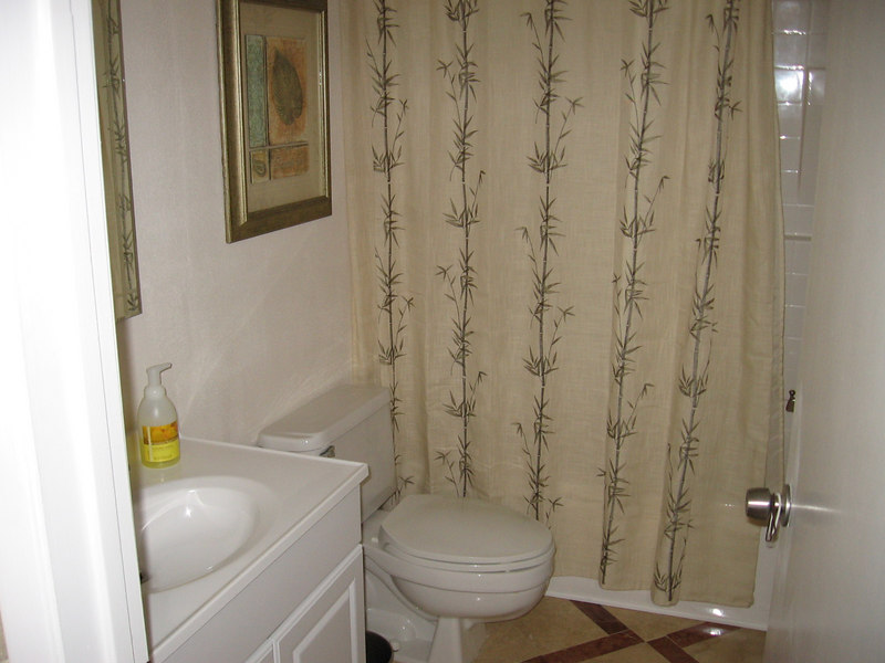 The bathroom has a new sink and shower, patterned travertine tile floors.