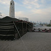 Bedouin's tent and primitive minaret contrast with modern Doha skyline in the distance.