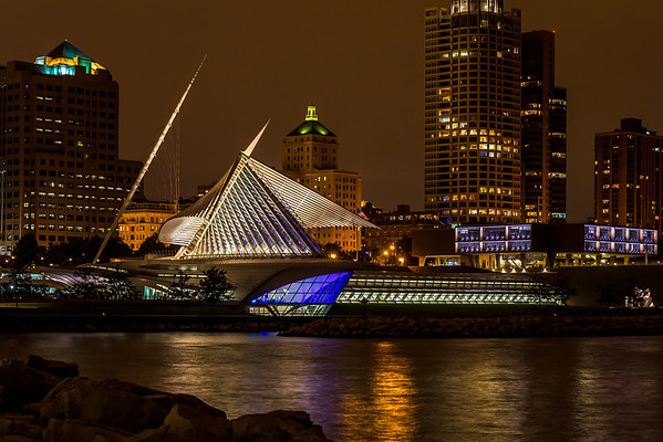 """The Milwaukee Art Museum and the Milwaukee Skyline on a beautiful September evening. At 30 mph. the """"wings"""" automatically close. On this evening the wind was picking up due to an incoming storm causing the """"wings"""" to fold before the party at the museum was over. With the cloudy sky reflecting the city lights as a yellow/orange glow as a backdrop, the scene was irresistible.<br/><br/><i><A href=""""http://chuck-de-la-rosa.artistwebsites.com/featured/colorful-evening-chuck-de-la-rosa.html"""" target=""""_blank"""">Click here to order prints of this photo!</A></i>"""