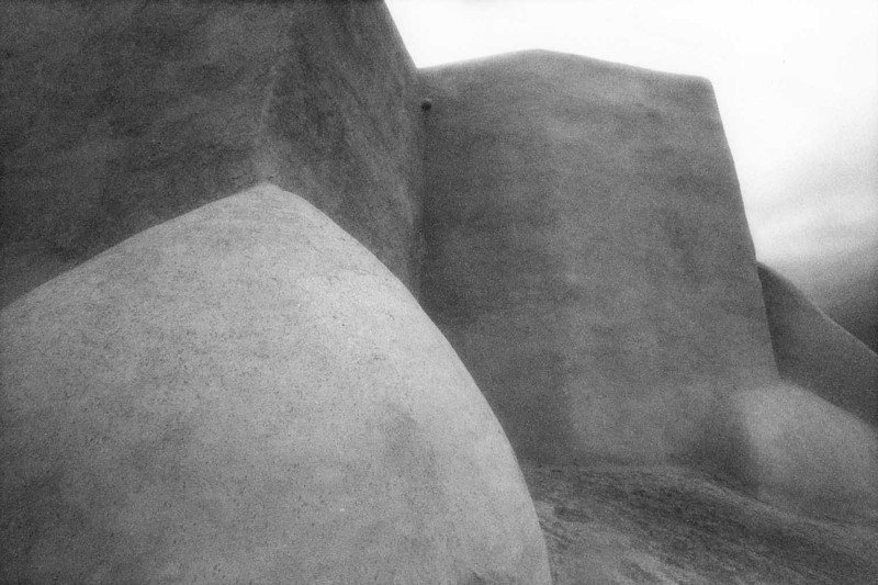 SAN FRANCISCO de ASIS MISSION CHURCH<br /> Rancho de Taos, New Mexico<br /> <br /> So I hung around and abstracted it even more, shooting totally with infrared film, even though it was drizzling rain. I can't believe it came out! What a lovely soft quality it has, which I don't believe would've happened with straight black-and-white film. I must get back to this place someday in the sunshine, though.