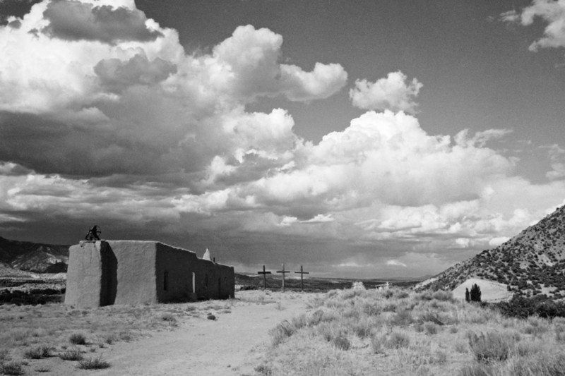 """PENITENTE MORADA Abiquiu, New Mexico  <i>Los Hermanos de la Fraternidad Piadosa de Nuestro Padre Jesús Nazareno</i> (in Spanish: """"The Brothers of the Pious Fraternity of Our Father Jesus the Nazarene"""", also known as <i>Los Penitentes</i>, <i>Los Hermanos</i>, and the <i>Penitente</i> Brotherhood) is a lay confraternity of Roman Catholic men very active in Northern New Mexico and southern Colorado. The men in these communities come together in the absence of a priest for the purpose of prayer, and to offer spiritual and social aid to the community. They gather in meeting houses known as <i>moradas</i>. <i>Los Penitentes</i> are perhaps best known for their songs of worship, called <i>alabados</i>, and for their ascetic practices, which include self-flagellation in private ceremonies during Lent, and processions during Holy Week which end with the re-enactment of Christ's crucifixion on Good Friday.  They're very protective of their religious beliefs and practices. My friends and I were ushered off the property at shotgun point."""