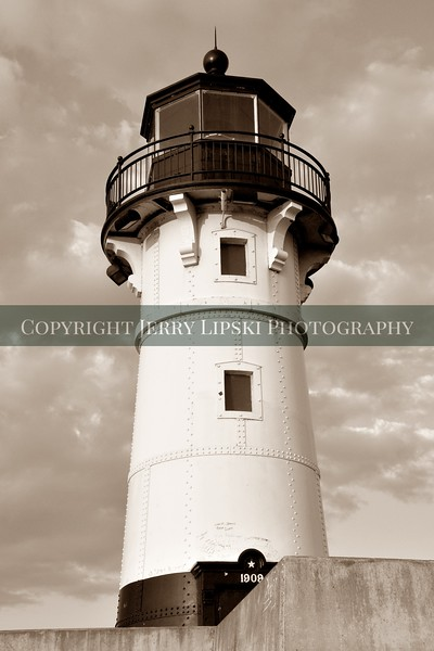 Image 3..................Sepia version of a 1909 lighthouse against a background of clouds on a cold Autumn day on Lake Superior.
