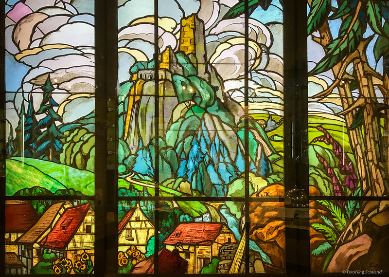 Jacques Gruber (1870-1935) Stained glass panels [3] in triptych form depicting a mountainous landscape.