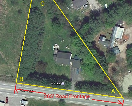 The property is 3/4 acre, shaped in a triangle.  It has 265 feet of road frontage on Rt. 121.  The road side and B-C side are edged with two rows of pine trees, one tall the other short.  The long back A-C side has a stone wall and deciduous trees.