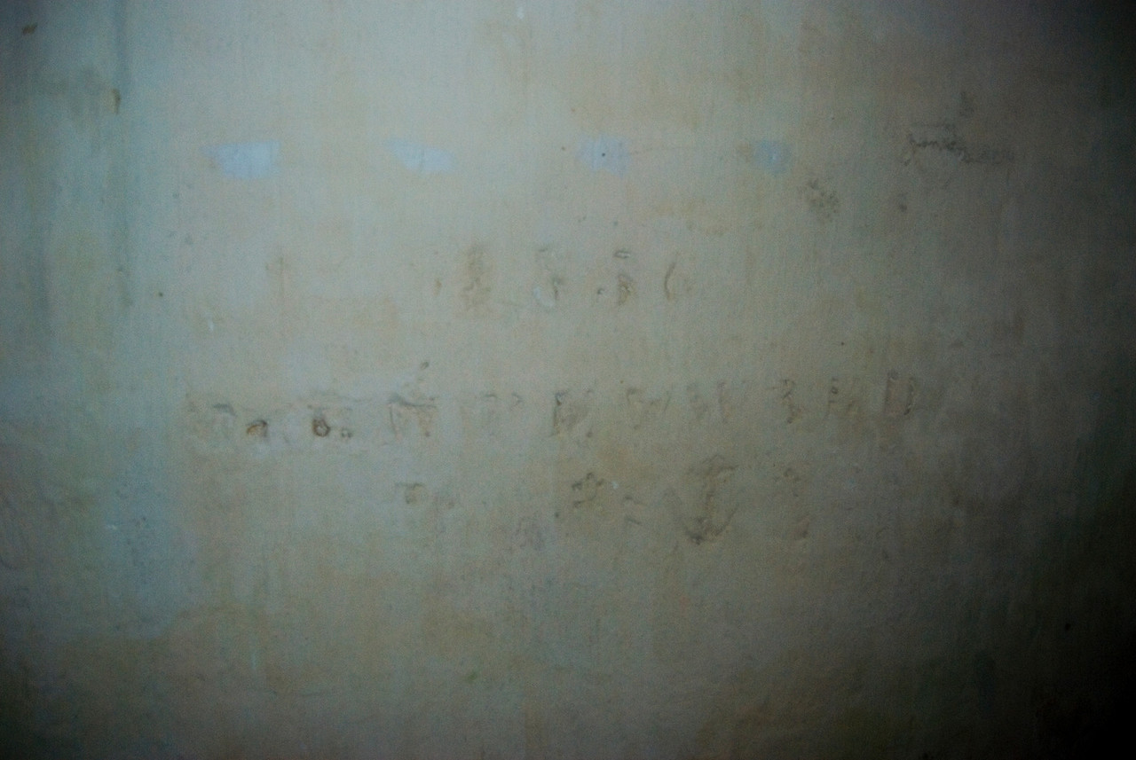 This is someones name and date carved into the cement wall.  No one has been able to completely decipher what it says though.