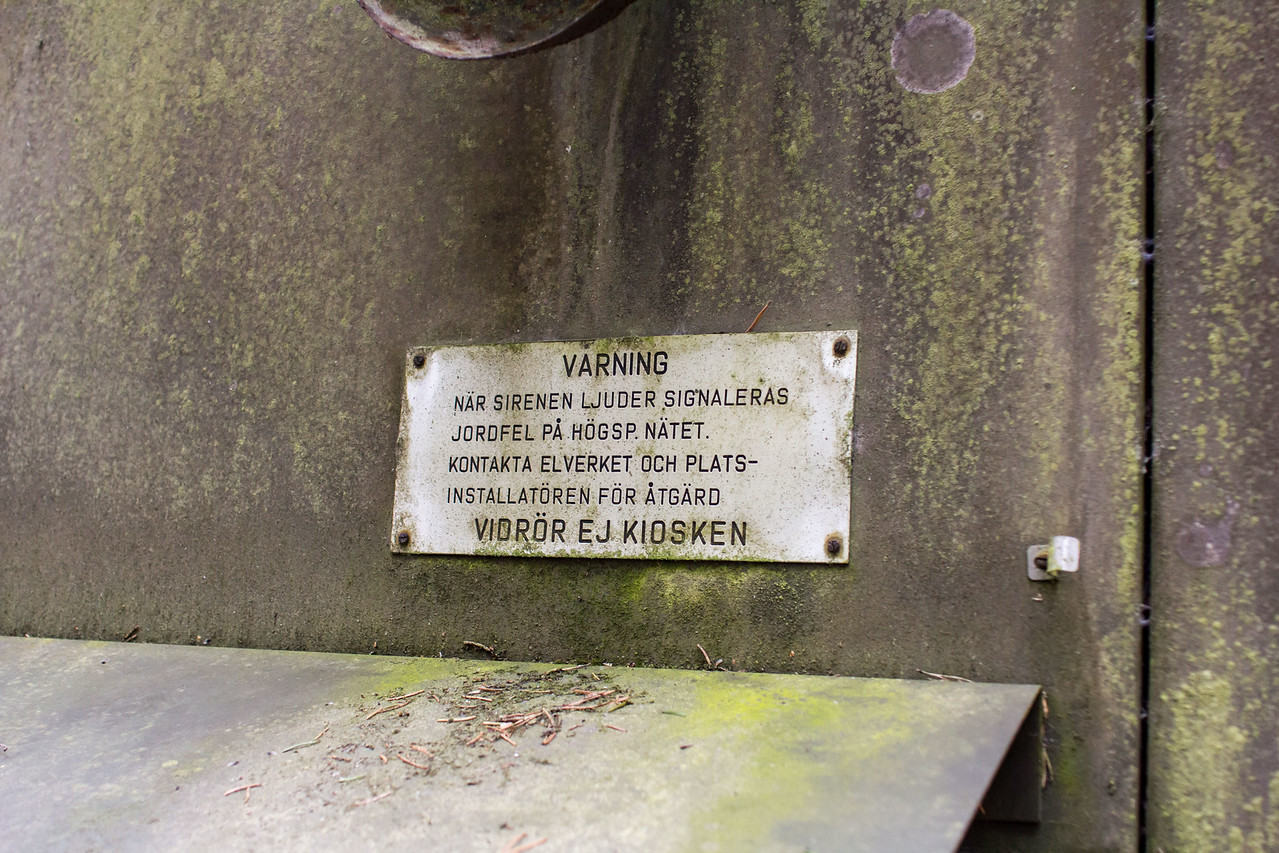 Translation from Swedish:  <br /> <br /> WARNING<br /> When the siren sounds signaled a ground fault in the high voltage network. Contact the supplier and the local caretaker for action<br /> <br /> DO NOT TOUCH KIOSK