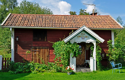 A view of the exterior of an old red cottage and garden in Sweden