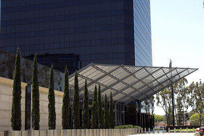 A modernistic walkway lined with stainless steel pliiars leading to a Southern California corporate office building