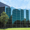 Modern corporate office building in Southern California built of reflective blue glass. Nicely landscaped with grass and evergreen trees
