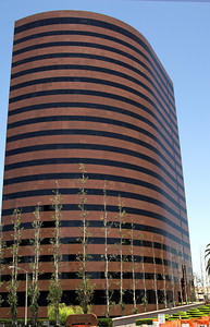 Rounded modern corporate office building in Southern California built of red marble and glass. Nicely landscaped with Poplar  trees