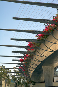Details of a modern walk bridge spanning a major road and connecting two sections of retail shopping centers