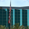 Modern corporate office building in Southern California built of reflective blue glass. Nicely landscaped with Date Palm trees and an American flag hanging slack