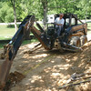Beemer John on the skid steer back hoe, starting the footers for the front wall.