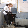 Pat helping me black the foundation (waterproofing)