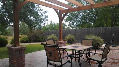 An intimate dining space defined by a cedar post and beam pergola.