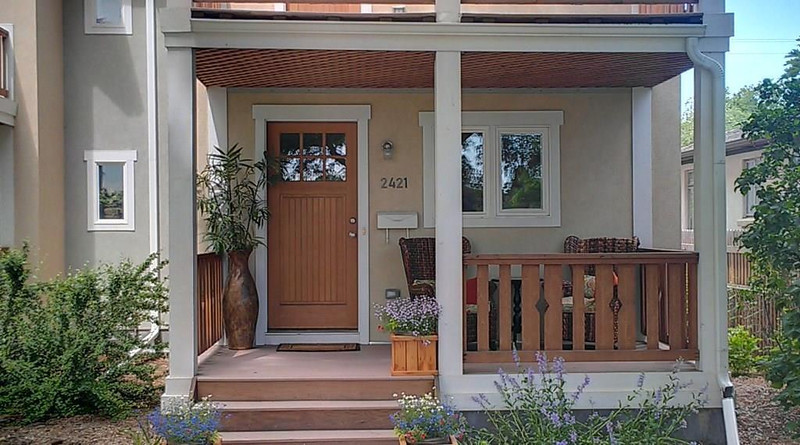 A charming covered front entry, personalized with plants and furniture.