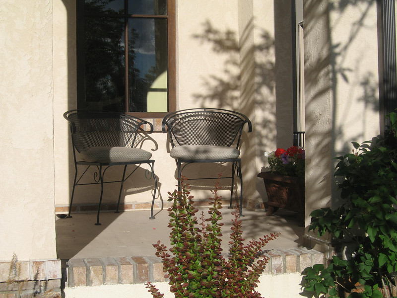 Flowers and plants add a bit of privacy to this front porch seating area.
