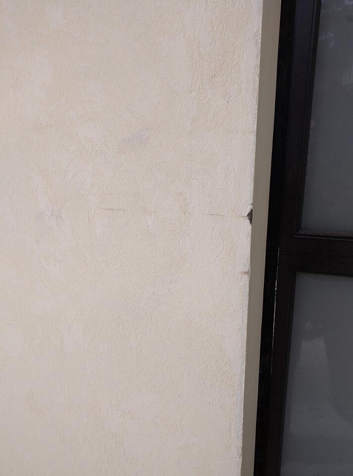 Big dent into scratch coat left of garage door