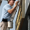 Flanagan Painters owner Joe Flanagan works on repainting the storefront at an attorneys office on Middlesex Street at Central Street. (SUN/Julia Malakie)