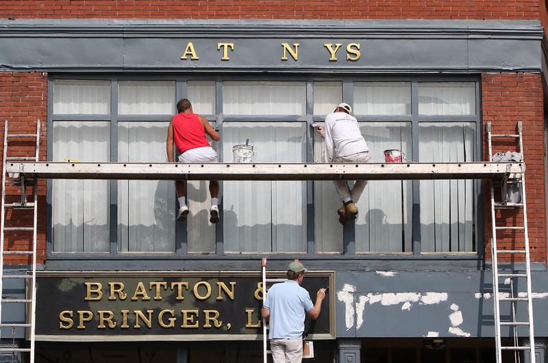"Flanagan Painters owner Joe Flanagan, bottom, and Rob, left, and Bob, right, repaint the storefront at an attorneys office on Middlesex Street at Central Street. A few letters were loose in ""Attorneys"" and will be put back. (SUN/Julia Malakie)"