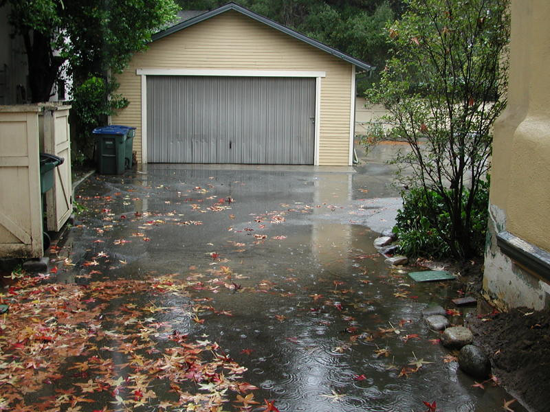 """Driveway flooding in December of 2010. The area drain is located next to the green box on the right side of the driveway. It was excavated and cleared but the top of the drain remains 2"""" above the driveway so the driveway still floods. The driveway grade should be raised and a concrete curb installed where the rocks are placed from the back wall to in front of the bay window. The planter grade could then be raised with inert decomposed granite which hardens and resists water. The water would run off quickly to the drain, or to the driveway in front of the bay window."""