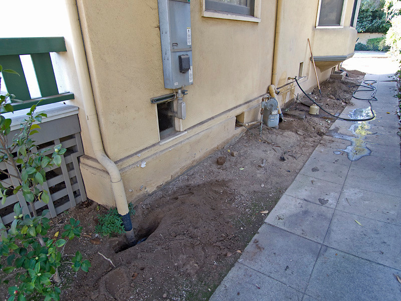 Photo taken December 4, 2009. The northeast corner of the Madison House at the front porch and the north side of the house. The sheet metal rain gutter downspout leader is connected to the subgrade plastic pipe and is working. The drain pipe extends a few feet to the left (east) and then turns north at a 45 degree angle, running under the sidewalk and into the adjoining property where it connects to a City drain pipe that also reportedly serves a condo complex behind the porperty. Surface area drains can be seen beyond. A hose flush indicated the drain pipes are open and working. In January, 2011, I installed a new surface area drain at the fence line and reconnected the drain pipe to the City drain beyond - just out of view to the lower right.