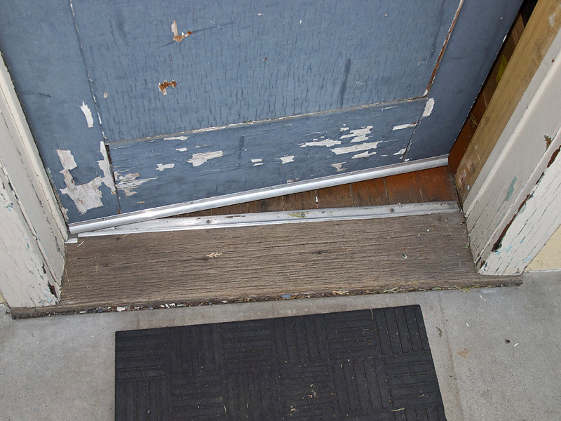 """The back door oak sill is badly weathered and splitting. The sill extends below the jambs but must be replaced in one piece. The concrete porch has been poured up to 1/2"""" of the top of the sill, creating a moisture trap at the sill. The sill must be replaced from below the floor after removing some of the settling floor supports. The separation of the door joints and sagging door can be seen here. For a new, thicker 1 3/4"""" door the door stops would be removed and replaced farther out on the jambs and the door would extend farther out over the sill. The wood threshold normally found covering the gap over the sill and floor is missing here. It was probably intentionally removed to keep the aceess less than 1/2"""" high for ADA compliance. See the other photos of the floor."""
