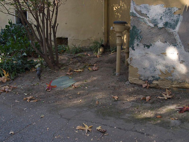 Photo taken December 4, 2009. The southwest corner of the Madison House at the corner of rthe driveway. Notice the sheet metal rain gutter downspout leader is separated from the subgrade plastic pipe. The two plastic landscape boxes in the foreground contain sprinkler control valves. A surface area drain is buried between the two green boxes. Compare the stucco plaster damage in December, 2009 to what has occured in one year, as shown in photos from December 2010. The green moss or algae growing on the ground indicates this area stays wet, and in fact, ponding has been observed at the corner of the driveway.
