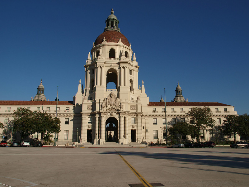 Pasadena City Hall was built in 1927 to inspire a city with beauty, boldness and vision. It is an important part of this community's rich architectural heritage.<br /> Pasadena City Hall was designed by John Bakewell & Arthur Brown who were influenced by the early Renaissance style of 16th century Italian architect Andrea Palladio. Construction was completed on December 27, 1927.   <br /> City Hall, located at 100 North Garfield Avenue, is a rectangular edifice outlining a spacious court.  On the outside it measures 351 feet north and south, and 242 feet east and west.  The east side is a one-story arcade.  The other three sides are three stories high, with small towers at each corner and the main dome over the west entrance.  The 235 rooms and passageways cover 170,000 square feet. <br /> The massive circular structure rises perpendicularly for six stories.  The fifth story is 41 feet high and pierced with four huge round arches and four smaller ones.  The next story, set back a little, is 30 feet high and is also pierced with arches.  Above it rises the dome 26 feet high and 54 feet across.  On top of the dome is the lantern, a column-supported cupola 41 feet high, surmounted by an urn and ball.  The highest point is 206 feet above the ground.