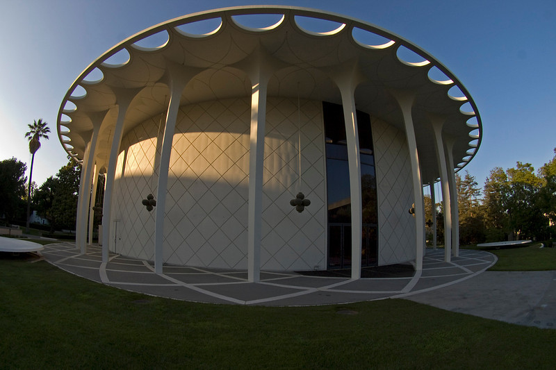 """Beckman Auditorium, Caltech Campus, Pasadena, CA. Beckman Auditorium is round, inside and out. It was designed by Edward Durrel Stone and built in 1964. The curved lobby is on this front side behind the glass doors, wrapping around the interior round walls at the back of the auditorium seating. The theater and stage are more conventional inside, with seating facing the stage in somewhat arched rows. There's a balcony as well. I think it seats about 1200 people. The auditorium walls inside are round and covered in fabric from the stage to the back wall behind the seating. The padded round walls provide excellent acoustics, since none of the sound is bounced back and forth like you get with hard parallel walls such as in a gymnasium or an empty room. The ceiling has 'gold' discs on strands radiating from the center, which adds a rich Modern look. """"Gold"""" emblems or stars dot the fabric walls. It's quite a spectacular place. I've attended more than a few good concerts and film festivals at Beckman Auditorium. Olympus E-3 and 8 mm f/3.5 fish eye lens."""