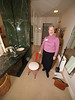 Volunteer, Cathy Phelps and a Frank Lloyd Wright designed chair. Remember, this is an ultra wide angle photograph so elements close to the camera look bigger than they really are. The door is just a few feet back but looks to be half the size of Cathy. With this lens everything at the edges of the frame is pulled into the corners and distorted. The basket is actually right at my feet and the vanity wall expands into the top of the frame.